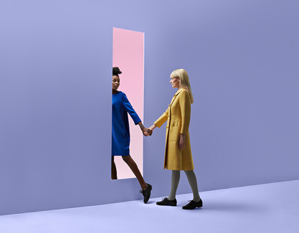 Two women hold hands, in a colored, minimalistic studio setting