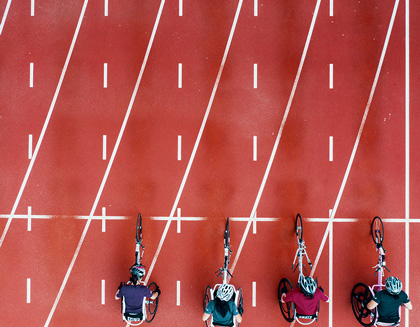 View from directly above four women racing in wheelchairs at the starting line