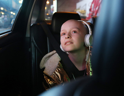 A young cancer patient rides in a car wearing headphones